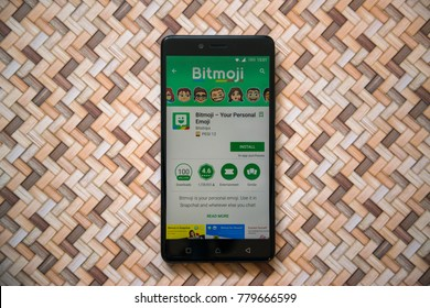 Los Angeles, USA, december 20, 2017: Bitmoji app in google play store on smartphone screen on wooden parquet floor background