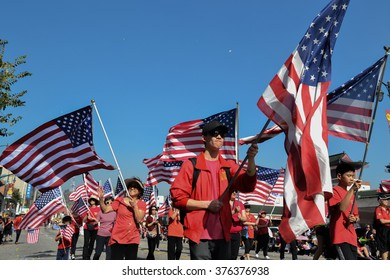 Los Angeles, USA - February 13, 2016: Participants with American flags during the 117th Golden Dragon Parade, celebrating Chinese New Year and the Year of the Monkey.