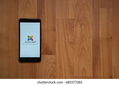 Los Angeles, USA, july 13, 2017: Joomla logo on smartphone screen on wooden background.