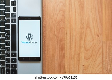 Los Angeles, USA, july 18, 2017: Wordpress logo on smartphone screen placed on the laptop on wooden background.