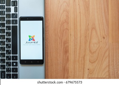 Los Angeles, USA, july 18, 2017: Joomla on smartphone screen placed on the laptop on wooden background.