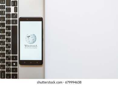 Los Angeles, USA, july 18, 2017: Wikipedia logo on smartphone screen placed on the laptop on white background.