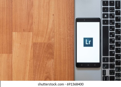 Los Angeles, USA, july 18, 2017: Adobe photoshop lightroom on smartphone screen placed on the laptop on wooden background.