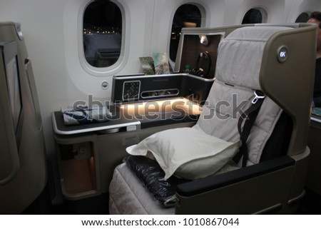 LOS ANGELES, USA TO MELBOURNE, AUSTRALIA FLIGHT – DECEMBER 17 2017: Qantas flight QF96 welcomes guests into its Boeing 787 business class cabin, including an unidentified passenger in the background.
