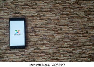 Los Angeles, USA, october 19, 2017: Joomla logo on smartphone screen on stone facing background