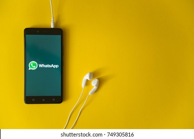 Los Angeles, USA, october 23, 2017: Whatsapp logo on smartphone screen and earphones plugged in on yellow background.