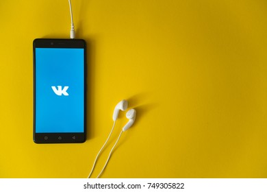 Los Angeles, USA, october 23, 2017: Vkontakte logo on smartphone screen and earphones plugged in on yellow background.