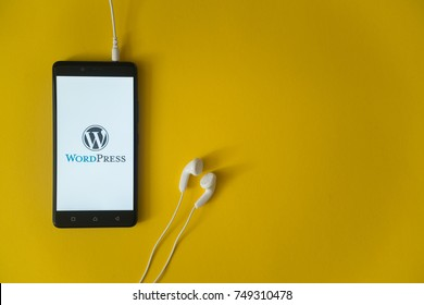 Los Angeles, USA, october 23, 2017: Wordpress logo on smartphone screen and earphones plugged in on yellow background.
