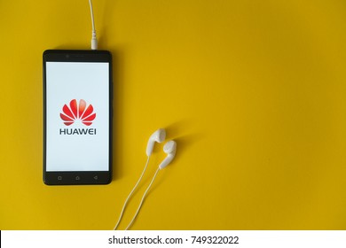 Los Angeles, USA, october 23, 2017: Huawei logo on smartphone screen and earphones plugged in on yellow background.