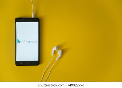 Los Angeles, USA, october 23, 2017: Google play logo on smartphone screen and earphones plugged in on yellow background.