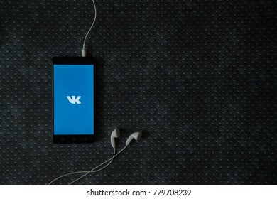 Los Angeles, USA, october 23, 2017: Vkontakte logo on smartphone screen and earphones plugged in on metal plate background.
