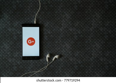 Los Angeles, USA, october 23, 2017: Google plus logo on smartphone screen and earphones plugged in on metal plate background.