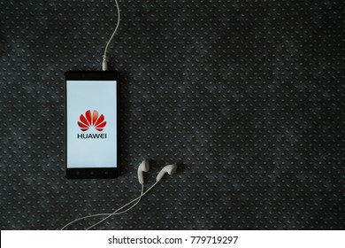 Los Angeles, USA, october 23, 2017: Huawei logo on smartphone screen and earphones plugged in on metal plate background.