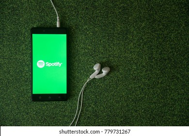 Los Angeles, USA, october 23, 2017: Spotify logo on smartphone screen on green grass background.