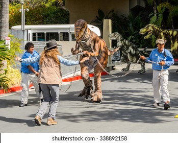 LOS ANGELES, USA - SEP 27, 2015: Velociraptor escorted by unidentified people in Jurassic Park area in the Universal Studios Hollywood Park. Jurassic Park is a 1993 adventure film