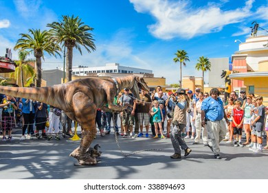 LOS ANGELES, USA - SEP 27, 2015: Unidentified girl tried to control a velociraptor in Jurassic Park area in the Universal Studios Hollywood Park. Jurassic Park is a 1993 adventure film  by Spielberg