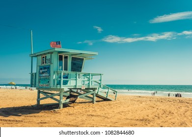 Los Angeles/California/USA - 07.22.2013: Lifeguard tower on the beach, people in the background swimming in the ocean and laying on the sand.