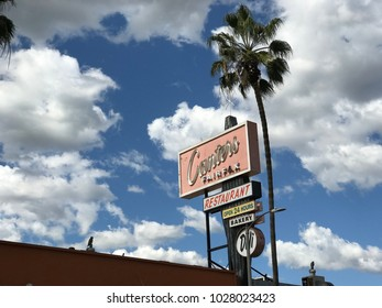 LOS ANGELES,FEB 13th 2018: Close up of the famous sign above Canter's Restaurant and Deli on Fairfax Avenue in the Fairfax District of Los Angeles, against a blue sky with white clouds and palms.