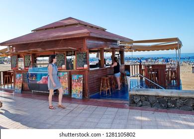 Los Cristianos, Tenerife / Spain - December 22, 2018 : Tourists buy snacks in a cafe on the beach boardwalk Las Vistas.