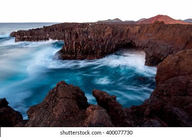 Los Hervideros rocky coast with wavy ocean and volcanos on the background on the sunset on Lanzarote island in Spain. Long exposure effect with blurred water