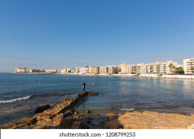 Los Locos Torrevieja Spain view across bay to beach and seafront with fisherman on the rocks