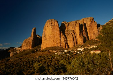 Los Mallos De Riglos rock formation and small village at foothill, colorful landscape lit by setting sun,environment of endangered Griffon Vultures