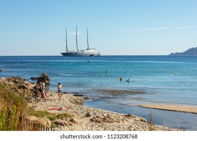 "LOSARI BEACH, CORSICA - 29TH JUNE 2018. A group of holidaymakers admiring the world's most expensive private yacht ""A"" moored at Losari beach in the Balagne region of Corsica"