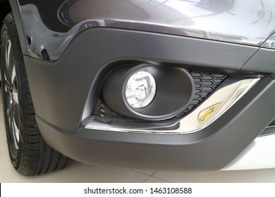 lose up headlamp SUV car parked on concrete parking. Automotive industry concept. Electric or hybrid car technology. Car rental concept. Detail on one of the LED headlights modern car.