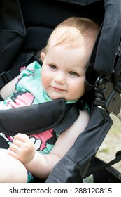 lose up Portrait of a Cute White Blond Baby girl on his Stroller, Looking Into the Distance.