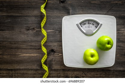 Lose weight concept. Bathroom scale, measuring tape, apples on wooden background top view copyspace