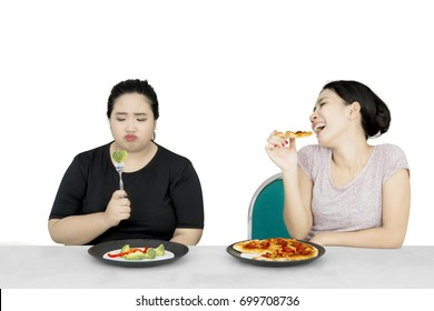 Lose weight concept. Unhappy overweight woman eating salad while her friend eating pizza with mocking expression