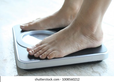 Lose weight concept, woman standing on scale measuring
