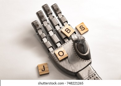 Lose your job to robots due to automation and the rise of the machines concept with a robot hand grabbing wooden tiles that spell out the word JOBS on white background