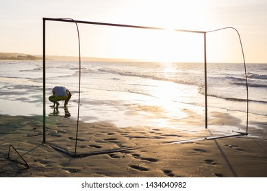 Loser and defeated goalkeeper alone and breakdown in the goal of a beach at sunset. Concept of frustration, discouragement on a game over football disappointment. Exhausted and sad sport competition.