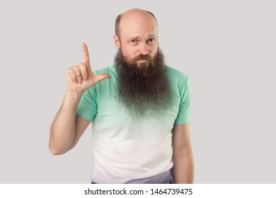 I am loser. Portrait of sad middle aged bald man with long beard in light green t-shirt standing with loser gesture and looking with failure face. indoor studio shot, isolated on grey background.