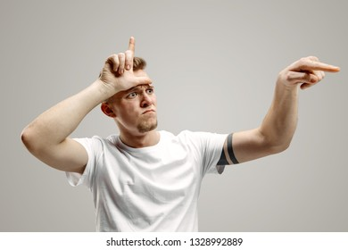 Losers go home. Portrait of angry guy showing loser sign over forehead over gray background