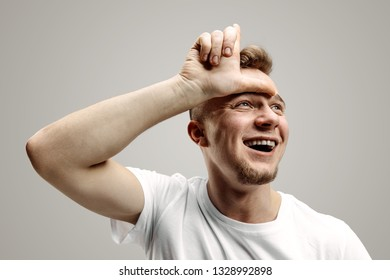 Losers go home. Portrait of happy guy showing loser sign over forehead and smiling in cause of victory and laughing over gray background