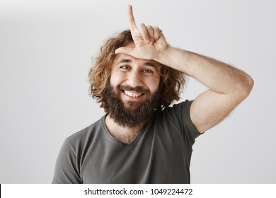 Losers go home. Portrait of scolding happy eastern guy with curly hair showing l sign over forehead and smiling broadly, bragging about victory and laughing over rival, standing over gray background