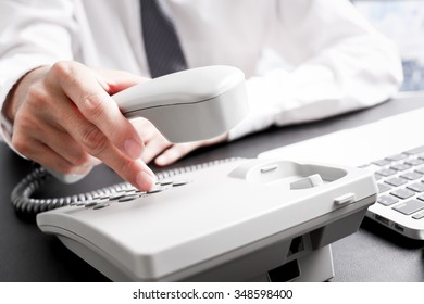 loseup of dialing a telephone number on a black landline telephone
