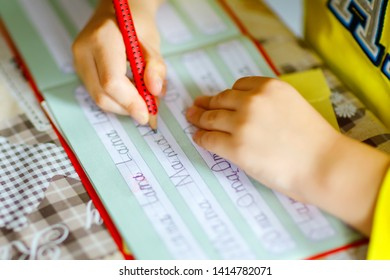 lose-up of little kid boy at home making homework, child writing first letters and words like mama with colorful pens. Elementary school and education