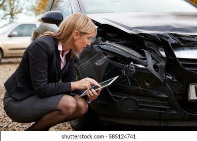 Loss Adjuster With Digital Tablet Inspecting Damaged Car