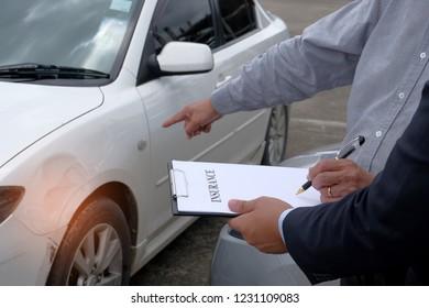 Loss Adjuster Insurance Agent Inspecting Damaged Car