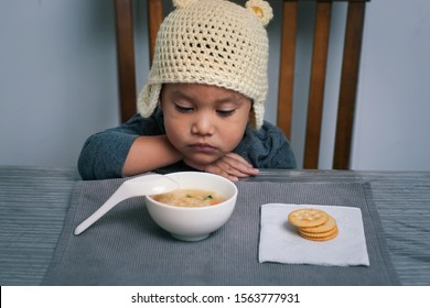 Loss of appetite for a sick toddler who is holding his sore throat with his hand and is staring at a bowl of homemade soup.