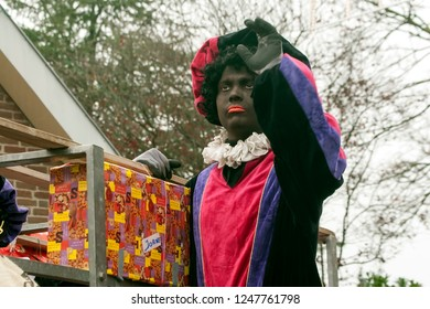 LOSSER, OVERIJSSEL / NETHERLANDS – NOVEMBER 17 2013: Black Piet with car of presents waving with his hand.