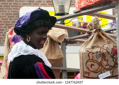 LOSSER, OVERIJSSEL / NETHERLANDS – NOVEMBER 17 2013: Black Piet by car with presents during entry St. Nicolas.
