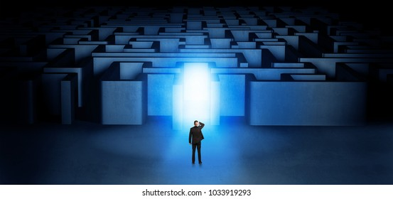 Lost businessman standing at the dark labyrinth with illuminated door