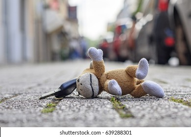 Lost car Keys on city pavement with plush monkey key ring