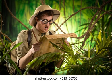 Lost explorer with glasses holding an old map looking for the right direction.