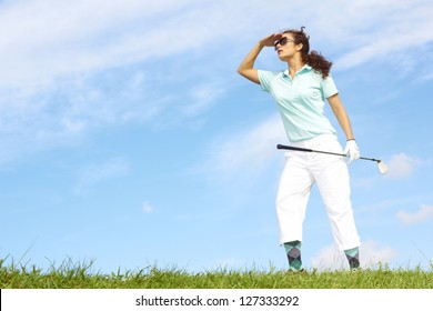Lost female golfer holding golf club looking for golf ball against clear blue sky. Wearing Sunglasses.