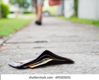 Lost leather wallet with money drop on sidewalk , lost money concept, copy space on top.
